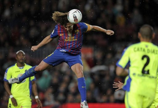 Barcelona's captain Carles Puyol heads the ball