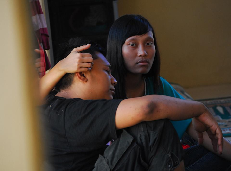 Survivors of the ferry accident on Sunda straits comfort each other at a temporary shelter in Cilegon, Banten province, Indonesia, Wednesday, Sept. 26, 2012. A passenger ferry collided with a cargo ship and sank west of Indonesia's main island Wednesday morning, and at least eight people were killed, officials said. (AP Photo)