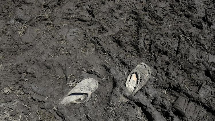 Abandoned flip flops are seen stuck in mud from recent rains at the New Orleans Jazz and Heritage Festival in New Orleans, Saturday, May 4, 2013. (AP Photo/Gerald Herbert)