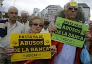 People hold placardds reading &quot;Enough with Bank abuses&quot; during a demonstration June 2, in Coruna. Spain&#39;s weak banks need at least 40 billion euros (US$50 billion) in new capital to strengthen against severe financial shocks, the International Monetary Fund said