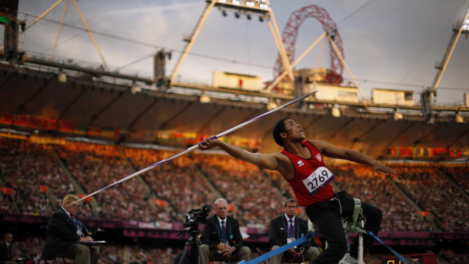 In light from the setting sun, Tunisia's Mohamed Ali Krid makes a throw in the men's javelin F34 category event during the athletics competition at the 2012 Paralympics, Saturday, Sept. 1, 2012, in London.  (AP Photo/Matt Dunham)
