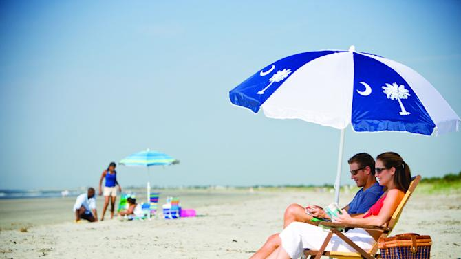 """In this file photo provided the Charleston Area Convention & Visitors Bureau, people sit on a beach in Kiawah Island, S.C. Nearby Beachwalker Park on Kiawah Island is tenth on the 2013 list of Top 10 Beaches produced annually by coastal expert Stephen P. Leatherman, also known as """"Dr. Beach,"""" director of Florida International University's Laboratory for Coastal Research. (AP Photo/Charleston Area Convention & Visitors Bureau, File)"""