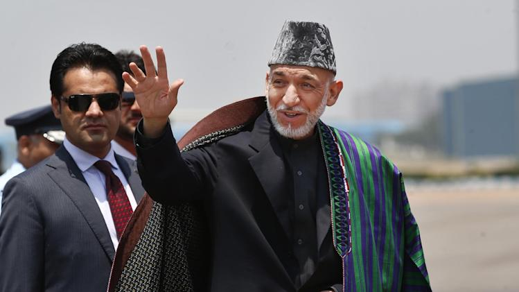 FILE - This May 26, 2014 file photo shows Afghan President Hamid Karzai in New Delhi, India. Civilian assistance to Afghanistan was always slated to shrink with America's military footprint, but U.S. aid officials were caught off-guard when Congress, upset by testy relations with Afghan President Hamid Karzai, slashed civilian aid by 50 percent this year. War-weary lawmakers, content with the level of Afghan aid already in the pipeline, backed the cut, but officials with the U.S. Agency for International Development warn that reducing aid too quickly is risky. (AP Photo/Saurabh Das, File)