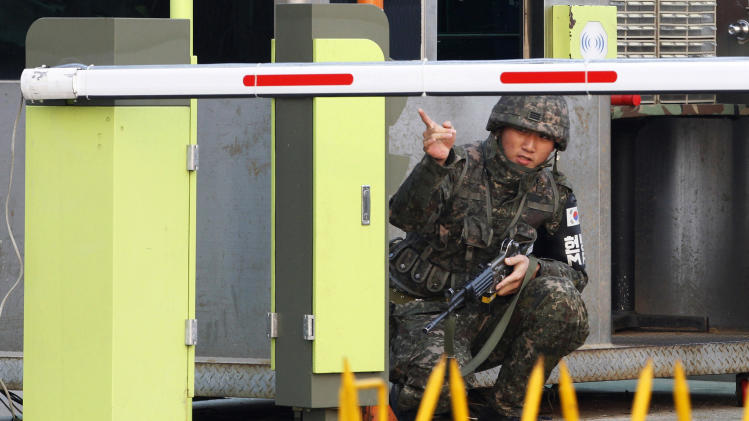 A South Korean Army soldier gestures at a military check point in Paju, South Korea, near the border village of Panmunjom, Thursday, April 4, 2013. North Korea on Wednesday barred South Korean workers from entering a jointly run factory park just over the heavily armed border in the North, officials in Seoul said, a day after Pyongyang announced it would restart its long-shuttered plutonium reactor and increase production of nuclear weapons material. (AP Photo/Ahn Young-joon)