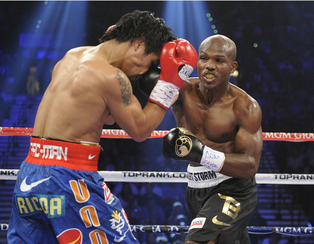Manny Pacquiao, from the Philippines, left, covers up as Timothy Bradley, from Palm Springs, Calif., throws a punch in the first round of their WBO world welterweight title fight Saturday, June 9, 201