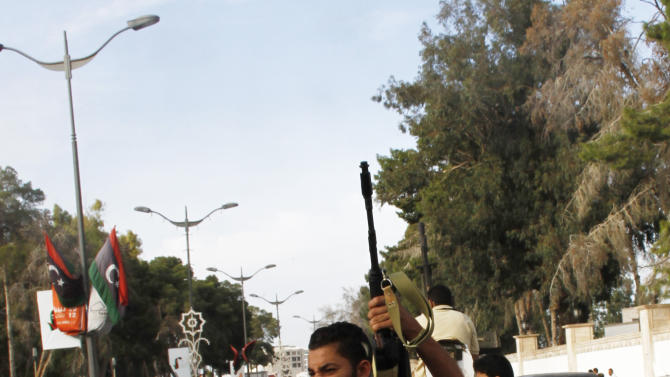 In this Sunday, Oct. 21, 2012 photo, a Libyan militiaman fires his weapon in the air in an attempt to force back protesters from in front of the gates of the parliament in Tripoli, Libya. One year on, the country is still trying to overcome the legacy of one of the most erratic leaders of modern times as well as a brutal eight month struggle that left the country awash in weapons, militias and very few viable institutions of the state. (AP/Paul Schemm)