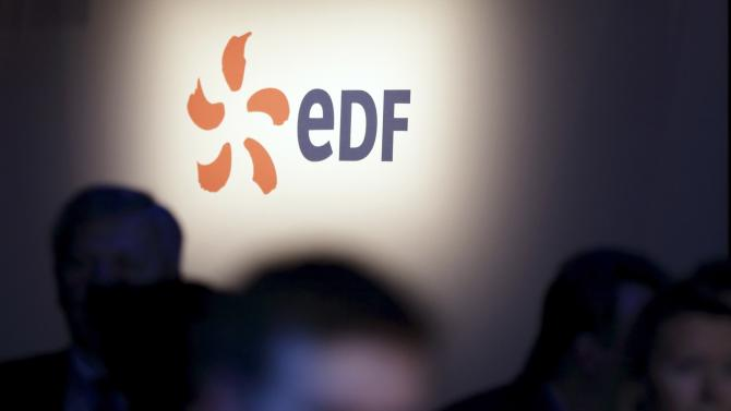 People walk past the logo of French state-owned utility EDF during the company's 2012 annual result presentation in Paris