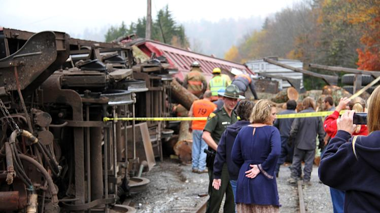 In this photo provided by the Pocahontas Times, crews work at the site where a truck carrying logs down Cheat Mountain on U.S. Route 250 crashed into the side of a train taking passengers on a scenic tour in rural Randolph County, W.Va., on Friday, Oct. 11, 2013. The crash killed one person and injured more than 60 others, according to emergency services officials. (AP Photo/The Pocahontas Times, Geoff Hamill)