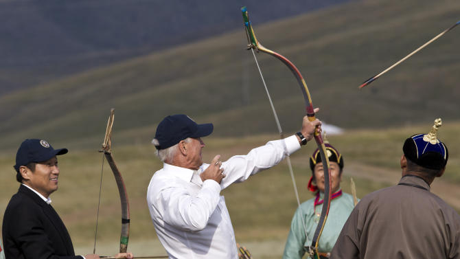 U.S. Vice President Joe Biden, center, accompanied by Mongolian Prime Minister Sukhbaatar Batbold, left, tries out an archery while on a tour at Mini Nadam or Mongolian wrestling performance in Ulan Bator, Mongolia, Monday, Aug. 22, 2011. (AP Photo/Andy Wong)