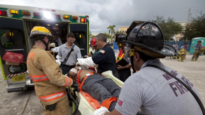 In a photo provided by Miami-Dade Fire Rescue, firefighters load a victim into an ambulance after a section of a parking garage under construction at a Miami-Dade College campus collapsed, Wednesday, Oct. 10, 2012 in Doral, Fla., killing one worker and trapping at least two others in the rubble, officials said. (AP Photo/Miami-Dade Fire Rescue)