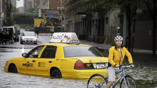 FILE - This Aug. 28, 2011 file photo shows a bicyclist making his way past a stranded taxi on a flooded New York City Street as Tropical Storm Irene passes through the city. Global warming-fueled sea level rise over the next century could at least flood 3.7 million people in the US, according to a new method of looking at flood risk published in two scientific papers.  (AP Photo/Peter Morgan, File)