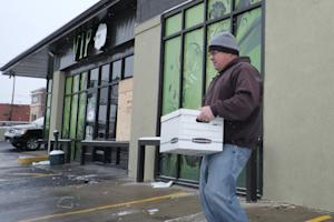 A federal agent carries a box from VIP Cannabis dispensary…