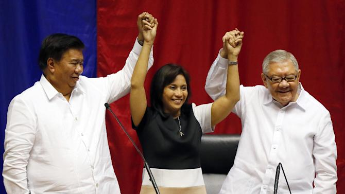 FILE - In this May 30, 2016 file photo, congresswoman Leni Robredo is proclaimed Philippine vice president elect by Senate President Franklin Drilon, left, and House Speaker Feliciano Belmonte during a ceremony at the Lower House in suburban Quezon city, northeast of Manila, Philippines. Robredo defeated Sen. Ferdinand Marcos Jr., son and namesake of the late dictator, in a cliffhanger race for vice president in May. (AP Photo/Bullit Marquez, File)