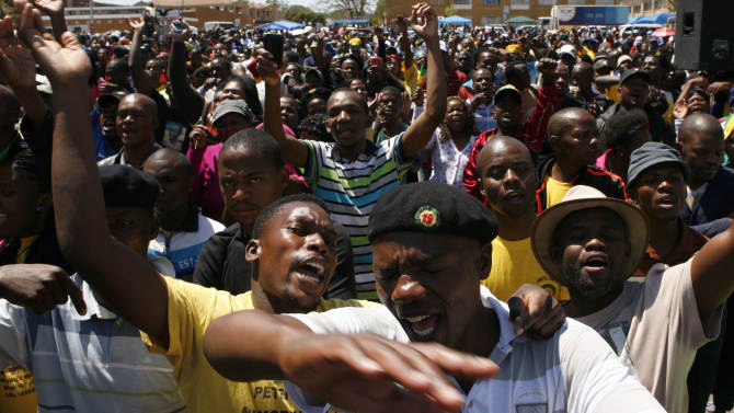 Supporters of a firebrand politician Julius Malema, unseen, sing before he is due to speak after appearing at the Magistrate's Court in Polokwane, South Africa, Wednesday, Sept. 26, 2012, on charges of money laundering in connection with an improper government tender awarded to a company his family trust partly owns. (AP Photo/Themba Hadebe)