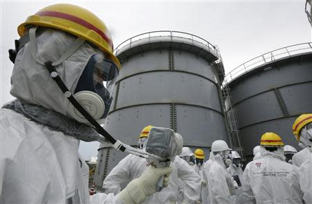File photo of TEPCO employee using a survey meter near storage tanks for radioactive water in the H4 area in Fukushima