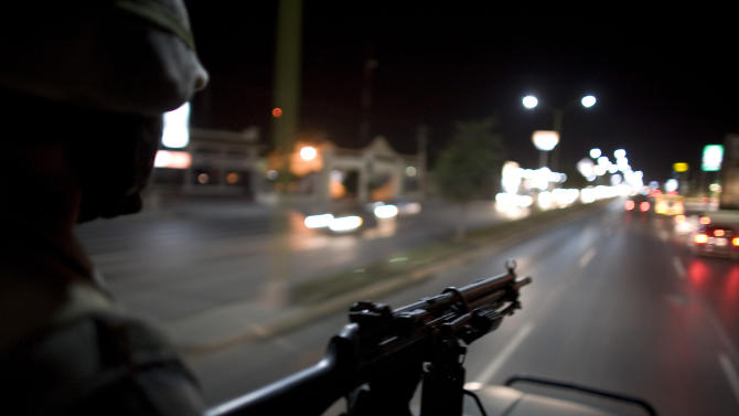 FILE - In this March 17, 2009 file photo, Mexican soldiers patrol the streets of Reynosa, on Mexico's northeastern border with the United States. On March 10, 2013, heavy gunfire echoed along the main thoroughfare and across several neighborhoods in a firefight that lasted for hours, leaving perforated and burned vehicles scattered across the border city. Social media exploded with reports of dozens dead. Witnesses saw at least 12, but an official count showed only a couple of deaths. (AP Photo/Alexandre Meneghini, File)
