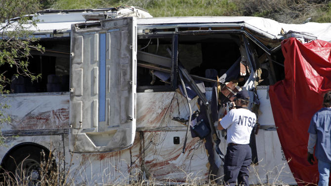 Bolldstains and personal items are seen as an investigator from the National Transpoartation Safety Board photographs a tour bus after an accident that killed at least eight people and 38 more were injured after a tour bus, left, carrying a group from Tijuana, Mexico crashed with two other vehicles just north of Yucaipa, Calif., Sunday, Feb. 3, 2013. (AP Photo/Reed Saxon)