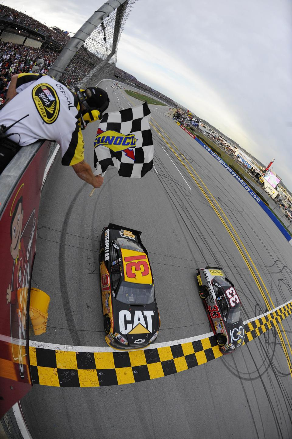 Clint Bowyer (33) crosses the finish line ahead of Jeff Burton (31) to win the NASCAR Sprint Cup Series auto race at Talladega Superspeedway on Sunday, Oct. 23, 2011, in Talladega, Ala. (AP Photo/Jason Smith, Pool)