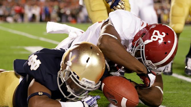 Alabama's Landon Collins (26) and Notre Dame's Davonte' Neal go after a fumbled punt during the first half of the BCS National Championship college football game Monday, Jan. 7, 2013, in Miami. The ball went out of bounds and Notre Dame retained possession. (AP Photo/David J. Phillip)