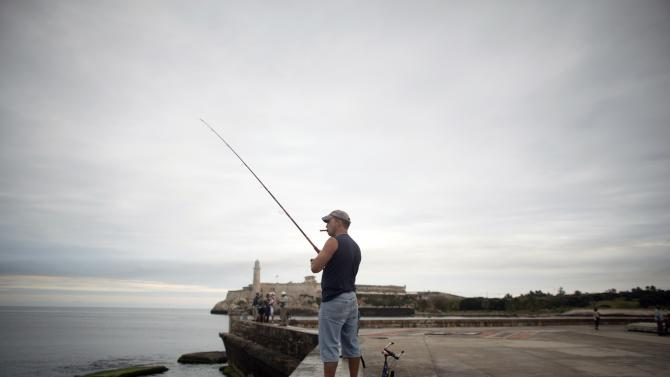 """A man fishes during his free time at the seafront boulevard """"El Malecon"""" in Havana"""