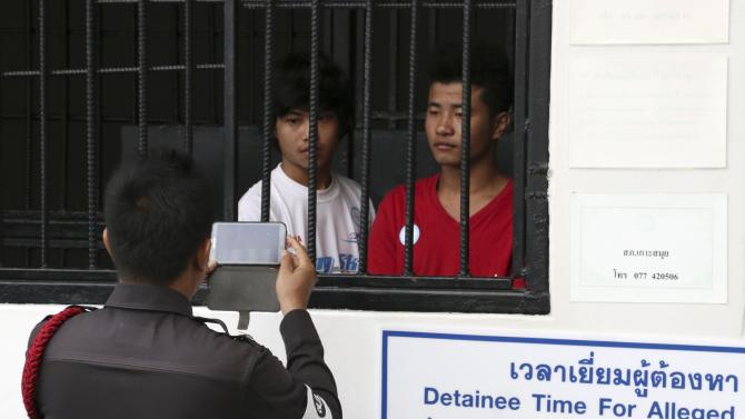 A policeman takes picture of Win Zaw Htun (L) and Zaw Lin, workers from Myanmar accused of killing two British tourists, at a court in Koh Samui