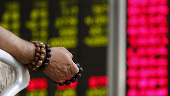 File photo of an investor holding onto prayer beads as he watches a board showing stock prices at a brokerage office in Beijing