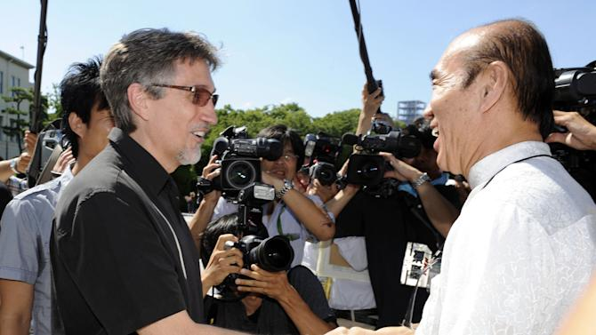 Clifton Truman Daniel, left, a grandson of former U.S. President Harry Truman, is greeted by Japanese peace activist Masahiro Sasaki who arranged Daniels' first visit to Japan, at the Hiroshima Peace Memorial Park in Hiroshima, Japan, Saturday, Aug. 4, 2012. Daniel laid a wreath at the park Saturday for the 140,000 people killed by the Aug. 6, 1945 bombing authorized by his grandfather. (AP Photo/Kyodo News)