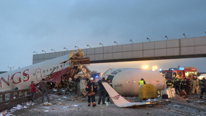 Rescuers work at the site where a plane careered off the runwaw at Vnukovo Airport in Moscow, Saturday, Dec. 29, 2012. A Tu-204 aircraft belonging to Russian airline Red Wings careered off the runway at Russia's third-busiest airport on Saturday, broke into pieces and caught fire, killing several people. (AP Photo/Alexander Usoltsev)