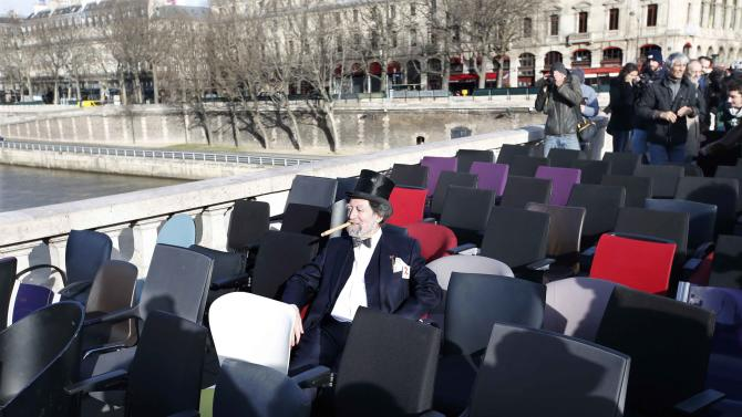 A demonstrator, dressed as a symbolic banker, sits on a chair next to empty ones that were stolen from bank offices in France to protest against the banking system and tax fraud, and installed on a bridge near the courts in Paris