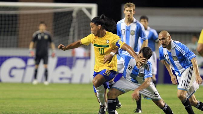 Brazil's Ronaldinho, left, is challenged by Argentina's Augusto Fernandez, second from left, during a soccer friendly match in Belem, Brazil, Wednesday, Sept. 28, 2011. (AP Photo/Lucivaldo Sena)