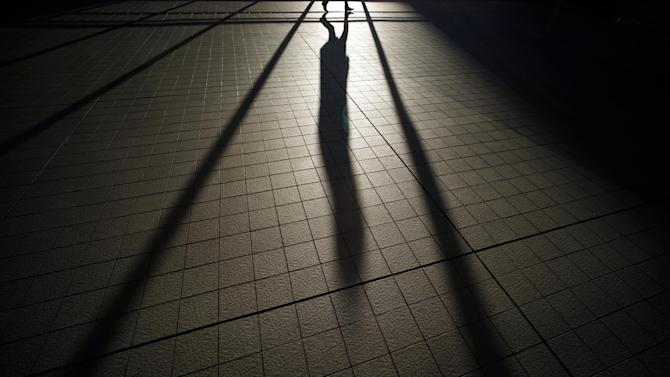 The shadow of a pedestrian falls on the floor of the train station in Tokyo, Thursday, Dec. 18, 2014. (AP Photo/Eugene Hoshiko)