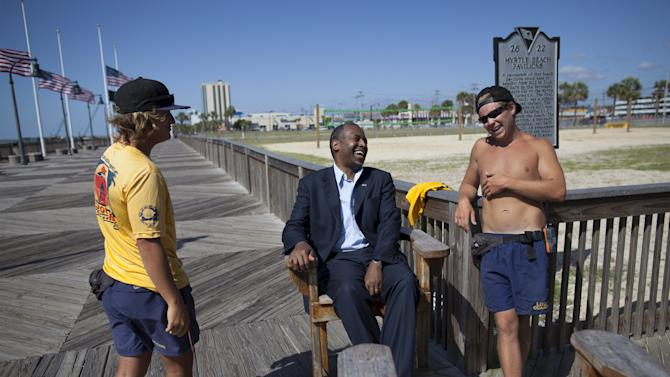 Republican presidential candidate Ben Carson laughs with Myrtle Beach lifeguards Matt Beeson (L) and Lane Cox on the boardwalk during a campaign event in Myrtle Beach