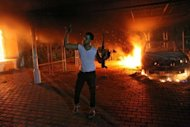 "An armed man waves his rifle as buildings and cars are engulfed in flames after being set on fire inside the US consulate compound in Benghazi on September 11. Mitt Romney on Wednesday hit out at the Obama administration's ""disgraceful"" response to violent protests in Egypt and Libya, accusing it of sympathizing with the Islamist demonstrators."