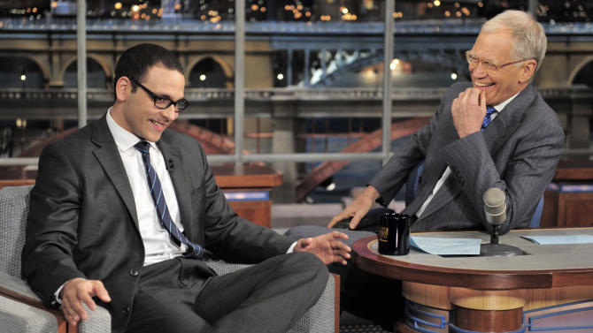 "In this photo provided by CBS, former news anchor A.J. Clemente, left, has a laugh with host David Letterman on the set of the ""Late Show with David Letterman,"" Wednesday, April 24, 2013 in New York. Clemente explained how he got fired on his first day from his television anchor job in Bismarck, N.D. (AP Photo/CBS, John Paul Filo)"
