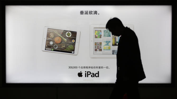A man walks by an advertisement of Apple's iPad in Shanghai, China, Tuesday, April 2, 2013. Apple apologized to Chinese consumers after government media attacked its repair policies for two weeks in a campaign that reeked of economic nationalism. (AP Photo/Eugene Hoshiko)