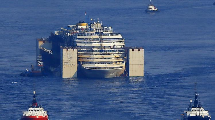 The wreck of the Costa Concordia cruise ship is towed by two tugboats along the Tyrrhenian sea, 30 miles off the coast of Viareggio, Italy, Friday, July 25, 2014. After more than two years since it slammed into a reef along the coastline of Isola del Giglio the wreck has been making its last journey, to the Italian port of Genoa, where it will be scrapped. Thirty-two people died when it hit the reef and started capsizing on Jan. 13, 2012. (AP Photo/Fabio Muzzi)