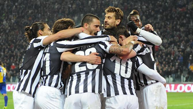 Juventus players hug their teammate Carlos Tevez, hidden at center, after he scored during a Serie A soccer match between Juventus and Parma at the Juventus stadium, in Turin, Italy, Wednesday, March 26, 2014