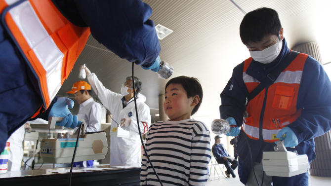 FILE - In this Friday, April 1, 2011 file photo, a boy is screened for radiation contamination before entering an evacuation center in Fukushima, Japan. Influential Japanese scientists who help set national radiation exposure limits have for years had trips paid for by the country's nuclear plant operators to attend overseas meetings of the world's top academic group on radiation safety. Some of these same scientists have consistently given optimistic assessments about the health risks of radiation, interviews with the scientists and government documents show. Their pivotal role in setting policy after the March 2011 tsunami and ensuing nuclear meltdowns meant the difference between schoolchildren playing outside or indoors and families staying or evacuating. (AP Photo/Wally Santana, File)