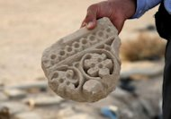 An Iraqi excavation official shows a broken archaeological piece at a pre-Islamic Christian monastery in the central city of Najaf on April 23, 2012. Christianity entered Iraq through Najaf but Christian archaeological sites in the city continue being neglected
