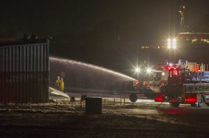 Firefighters work to extinguish fire at the site of …