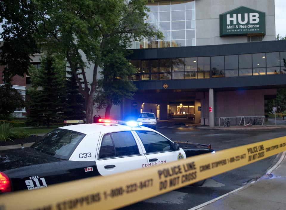 Police investigate the scene after three people were killed in an apparent attempted armed robbery at the University of Alberta in Edmonton, Canada on Friday, June 15, 2012.  The robbery happened in the Hub Mall area, which is a combination of student residences and 54 shops. (AP Photo/The Canadian Press, Ian Jackson)