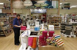An employee straightens a display in the home ware department at a Tesco Extra supermarket in Watford, north of London