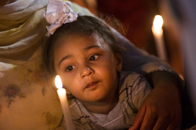 A child is held Tuesday Aug;.7, 2012 in Oak Creek, Wis., at a candle light vigil for the victims of a mass shooting at the Sikh Temple of Wisconsin on Sunday. The vigil was held during the national night out event at the Oak Creek Civic Center. (AP Photo/Tom Lynn)