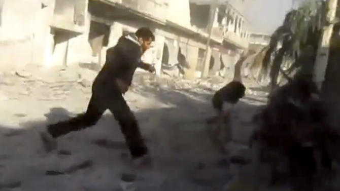 This image taken from video obtained from Shaam News Network, which has been authenticated based on its contents and other AP reporting, men running during heavy bombing from military warplanes in Houla, Syria, Tuesday, Nov. 6, 2012. The Britain-based Syrian Observatory for Human Rights said air raids on Houla, a group of villages in central province of Homs, killed several people.(AP Photo/Shaam News Network via AP video)