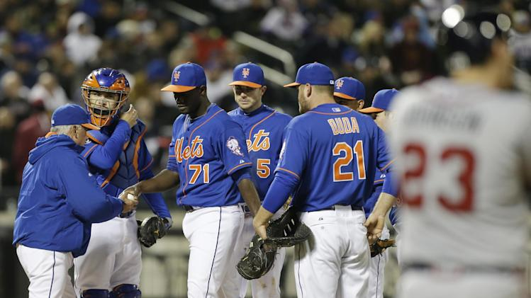 New York Mets manager Terry Collins, left, takes out relief pitcher Gonzalez Germen during the eighth inning of a baseball game against the Atlanta Braves, Friday, April 18, 2014, in New York. (AP Photo/Frank Franklin II)