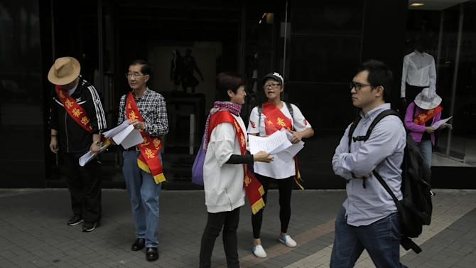 """In this Sunday, April 12, 2015 photo, a group of Hong Kong residents who support shoppers from the mainland China wearing red sashes with Chinese words: """"Hong Kong welcomes you"""" during a rally at a shopping district in Hong Kong. Eighteen years after this world financial hub returned from colonial British control to Chinese rule, many say they feel more alienated and less trusting than ever of the central Chinese government and even the people visiting from across the border. The complaints range from the small to the sweeping, from the perceived rudeness of Chinese tourists to fears that leaders in Beijing are sabotaging the freedoms and rule of law that have long distinguished Hong Kong from the rest of China. (AP Photo/Vincent Yu)"""