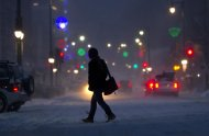 A woman crosses Congress Street during a snow storm, Friday, Feb. 8, 2013, in Portland, Maine. Snow began falling across the Northeast on Friday, ushering in what was predicted to be a huge, possibly historic blizzard and sending residents scurrying to stock up on food and gas up their cars. The storm could dump 1 to 3 feet of snow from New York City to Boston and beyond. (AP Photo/Robert F. Bukaty)
