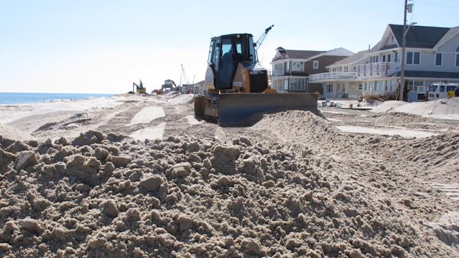 In this March 5, 2013 photo, a bulldozer piles up sand to help rebuild a dune in Lavallette N.J. Superstorm Sandy showed how dunes protect homes along the coast, yet not all oceanfront property owners want them, fearing lost waterfront views and fearing that giving the government permission to build bigger dunes could lead to construction of boardwalks or amusements behind their pricey homes. (AP Photo/Wayne Parry)