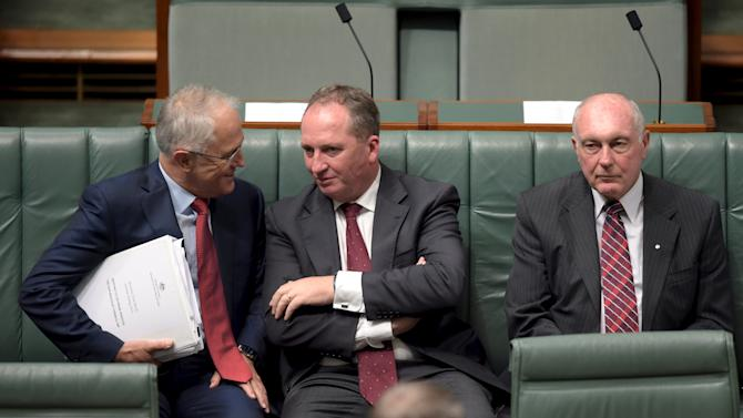 Australian Prime Minister Malcolm Turnbull speaks to Australian Agriculture Minister Barnaby Joyce as Federal Minister for Infrastructure and Regional Development Warren Truss sits next to them in Parliament House in Canberra