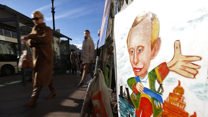People walk past a cartoon depicting Russia's President Vladimir Putin displayed by a street artist in St.Petersburg, Russia, Sunday, Oct. 7, 2012.  Vladimir Putin turns 60-years old on Sunday, Oct. 7, 2012, and has recently sought to demonstrate his youthful vigor by many personal endeavors, but while he has shown creativity in his action-man stunts, the Russian president seems surprisingly vulnerable to the vagaries of oil prices. (AP Photo/Dmitry Lovetsky)